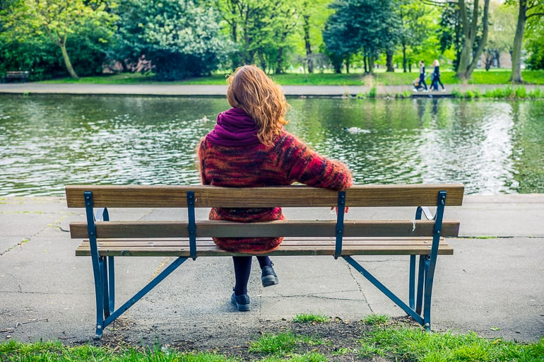 Photo of woman sitting on brown bench with lake and pathway in the background