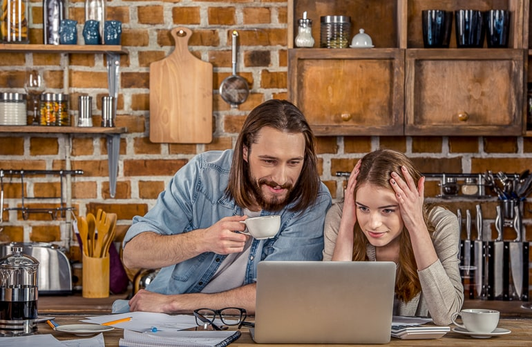Man and woman in kitchen looking at laptop screen with coffee next to them