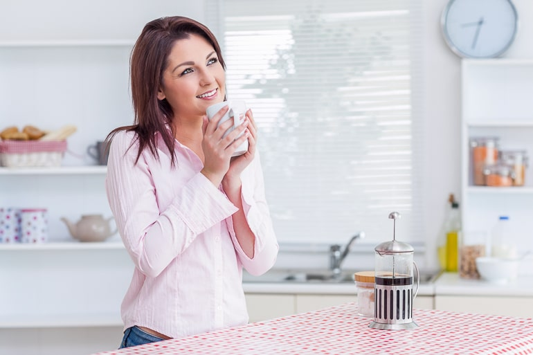 Woman standing and holding a mug with french press on counter in front of her