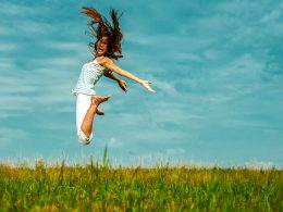 Woman jumping in air with green grass and blue sky how to be successful in life