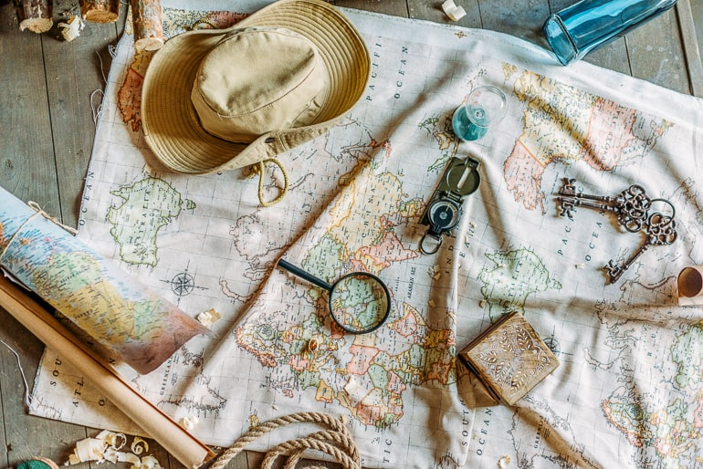 Map with hat compass keys and other things on wood floor