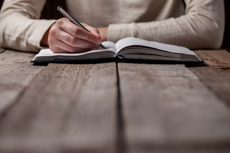 person writing in notebook on wood table