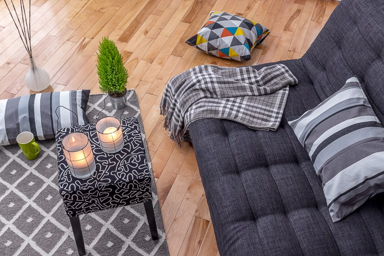 Couch with blankets and table with candles cope with moving away from loved ones