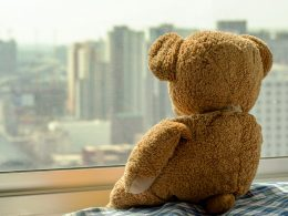 Brown Teddy Bear looking out a window how to cope with moving away from family and friends