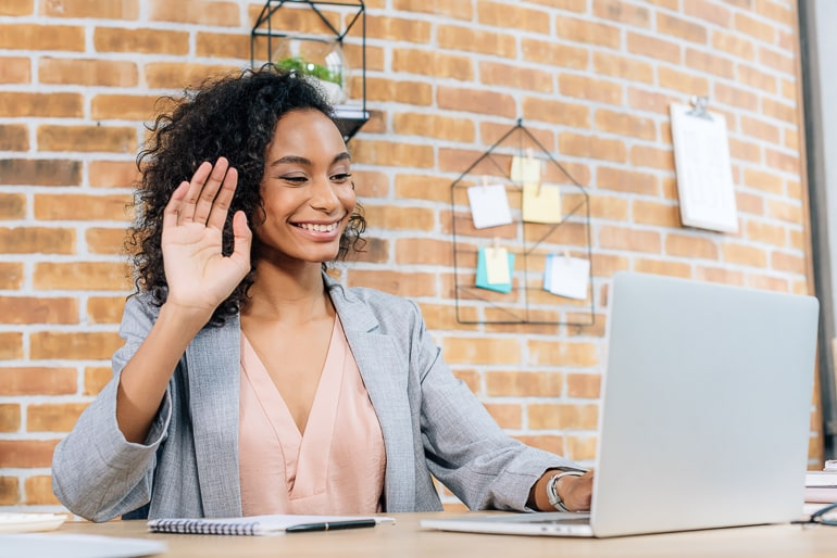 Woman sitting in front of computer and waving
