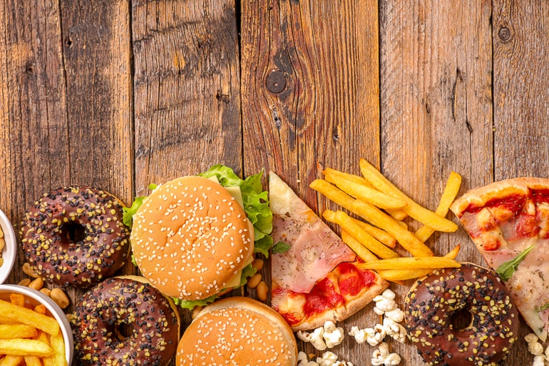 donuts burgers pizza and fries on wooden background