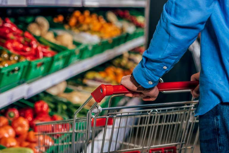 Hands holding a shopping cart in front of produce isle at grocery store