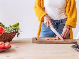 Woman cutting carrot on brown cutting board with bowls of fruit and vegetables next to it how to eat healthy on a budget