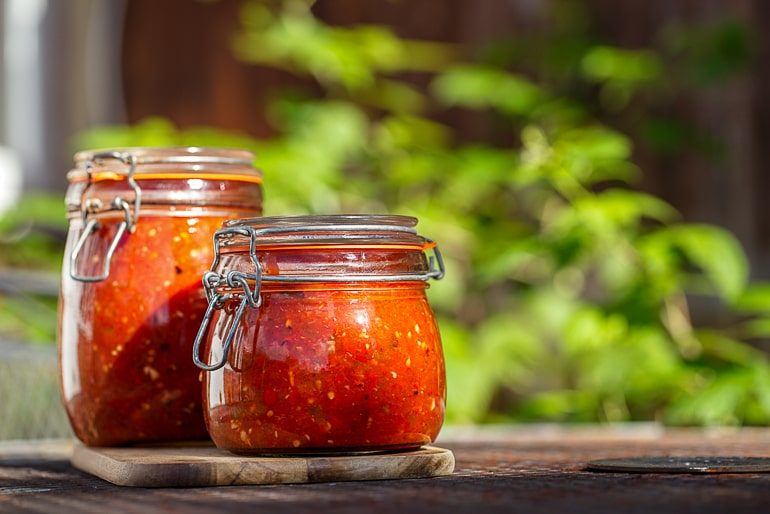 Two jars of homemade tomato sauce with green background