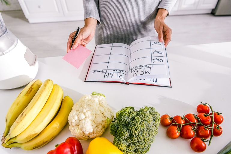 Woman holding meal plan table on counter with fruit and vegetables next to it