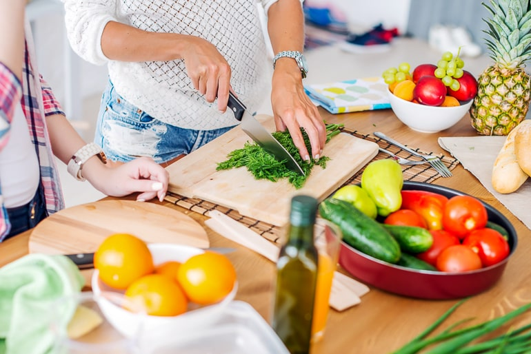 woman cutting herbs on cutting board with fruit and vegetables next to it