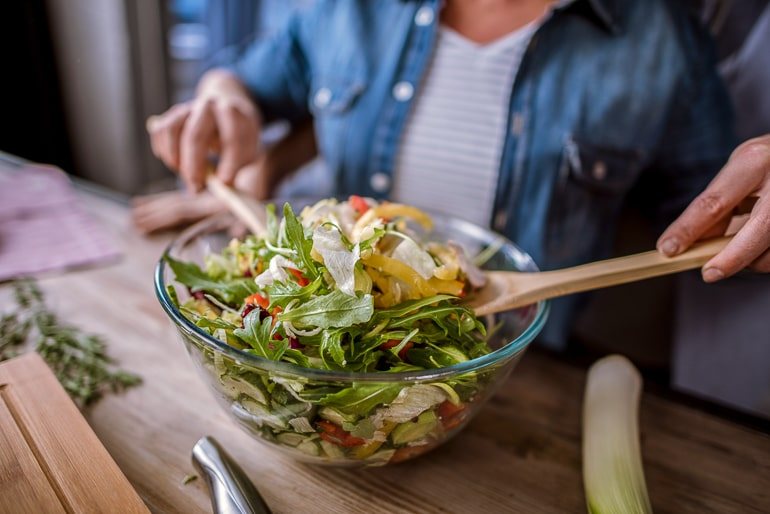 Glass bowl full of salad with person holding woden spoons