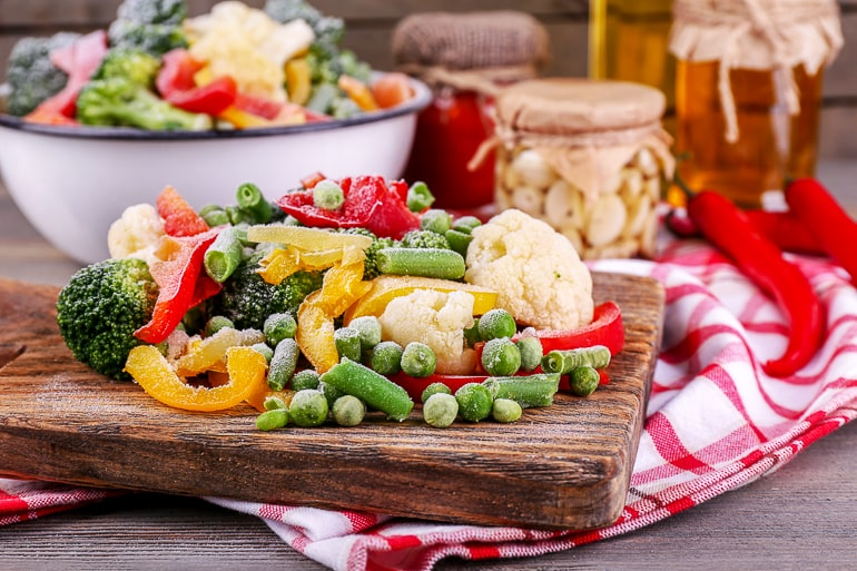 Frozen vegetables on brown cutting board eating healthy when busy