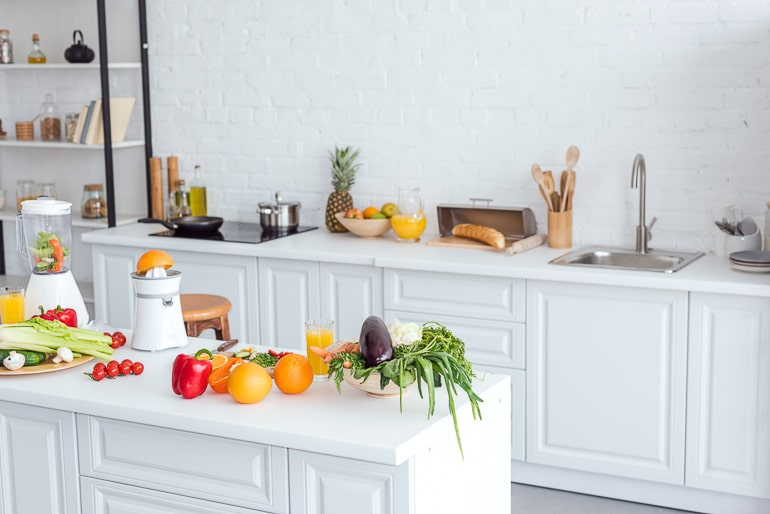 White kitchen with colorful fruit and vegetables on counter healthy eating