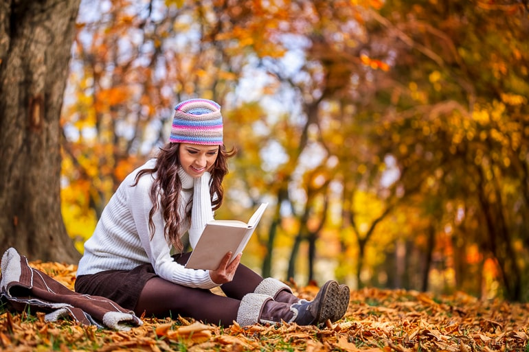 Woman with hat sitting on ground covered in fall leaves and reading a book