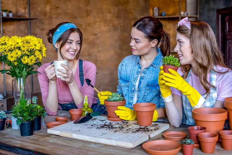 Three woman looking at each other while holding pots and plants in their hands gardening