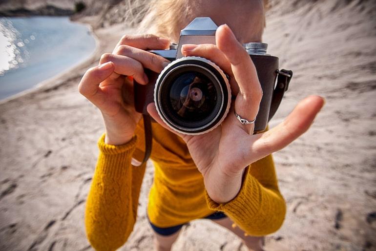 Closeup of woman in yellow shirt holding camera
