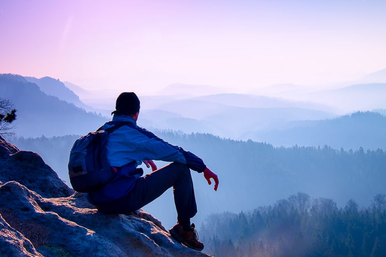 Guy with backpack sitting on rock and staring into distance how to not lose yourself in a relationship