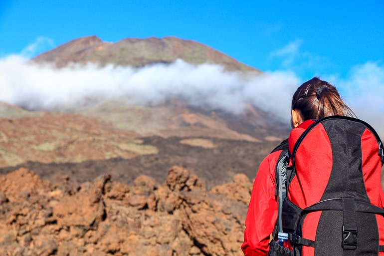 Woman with red jacket and backpack facing a rocky hill