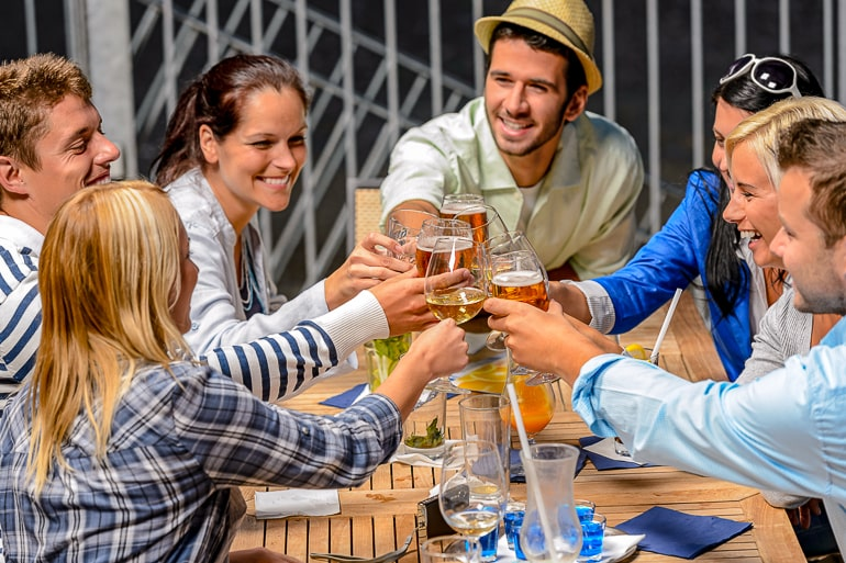 Group of friends raising glasses and laughing how to not lose yourself in relationship