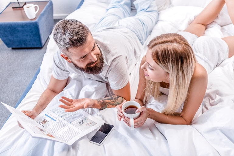 Man and woman laying in bed facing each other and talking while holding newspaper and mug