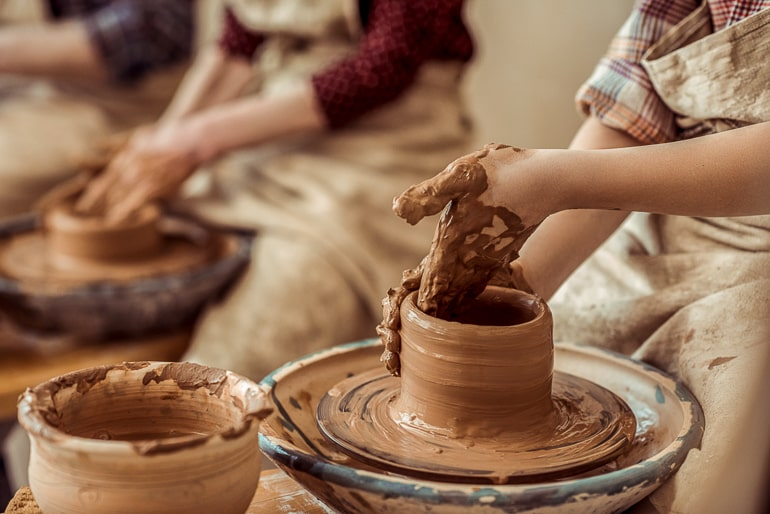 Hands shaping clay on pottery wheel