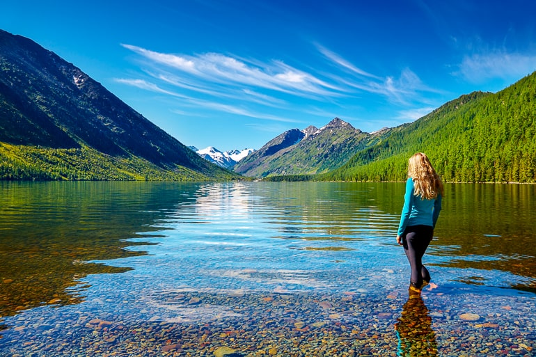 Woman with blonde hair standing in clear water with mountains and forest in background