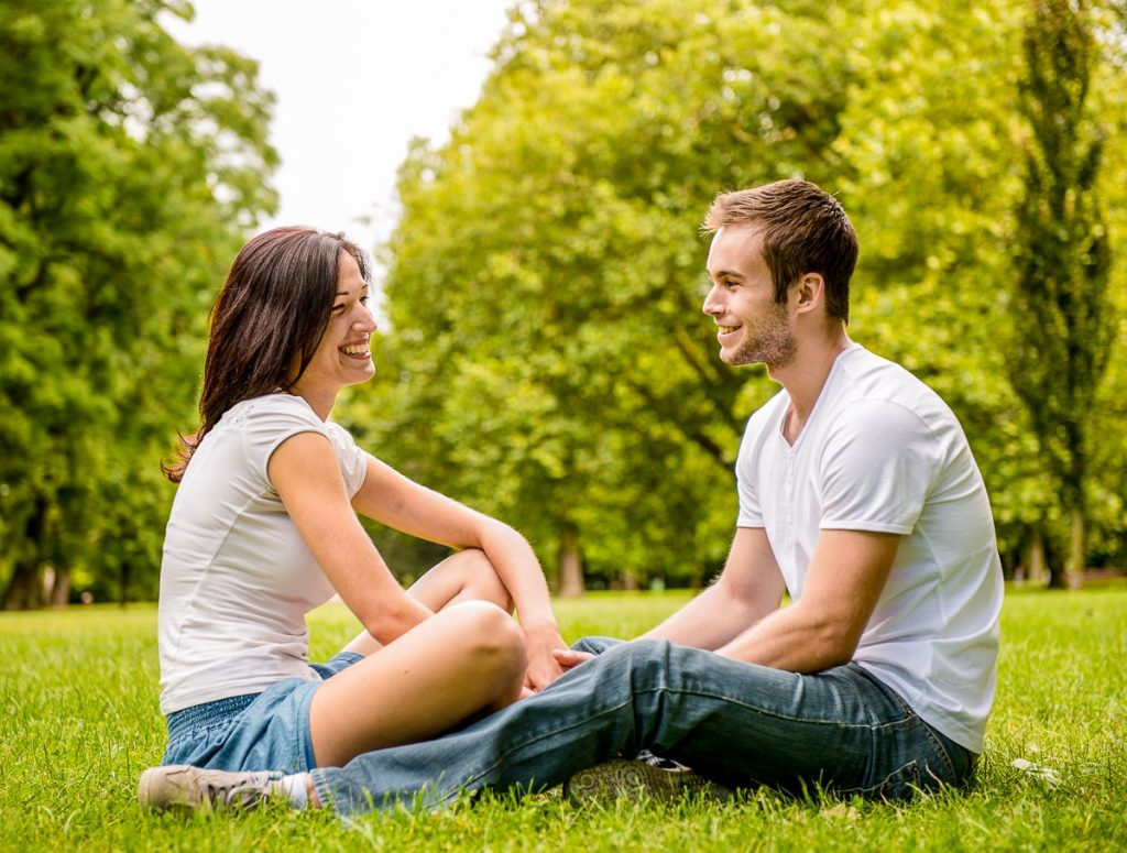 Man and woman sitting in park looking at each other and smiling how to not lose yourself in a relationship