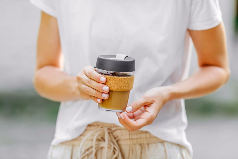 Person holding reusable coffee mug
