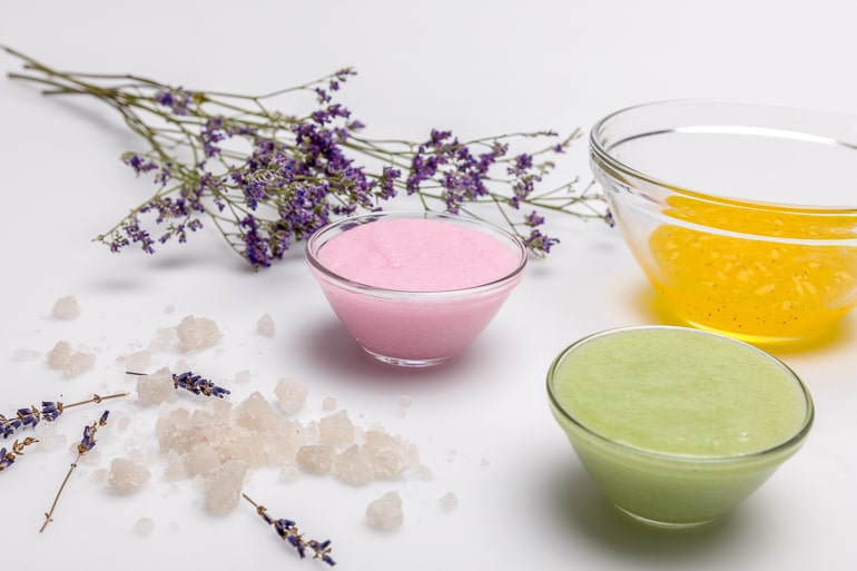Homemade beauty products in glass bowls with lavender next to them