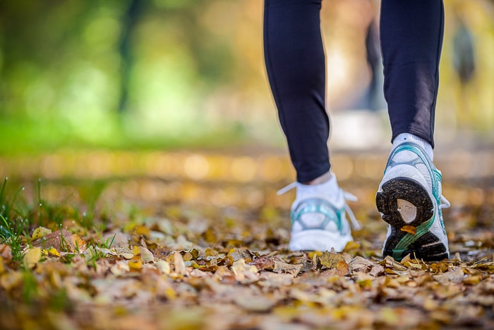 legs with running shoes walking on autumn leaves