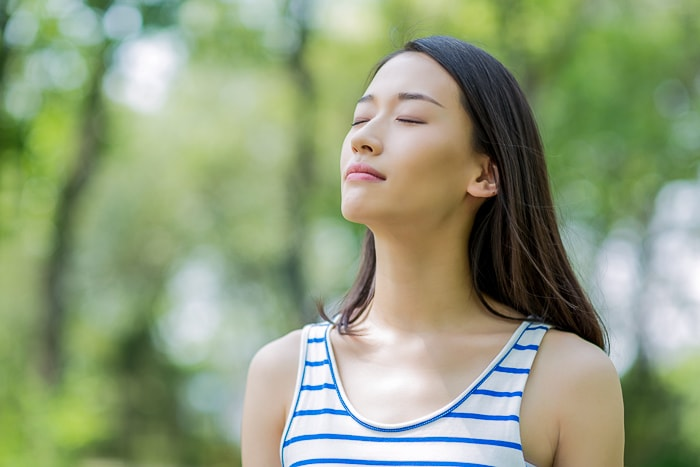 woman with striped top breathing outside in forest how to stop an anxiety attack