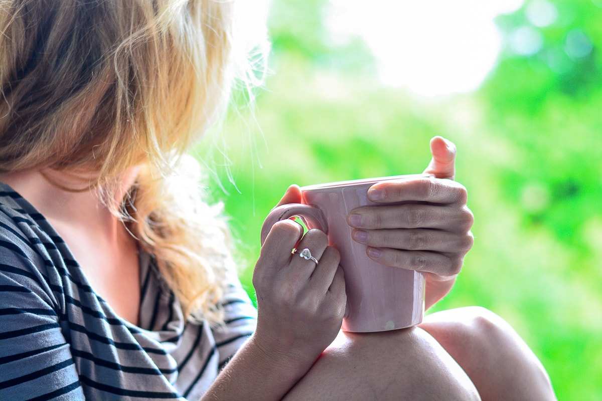 woman sitting with pink mug looking out window how to stop an anxiety attack