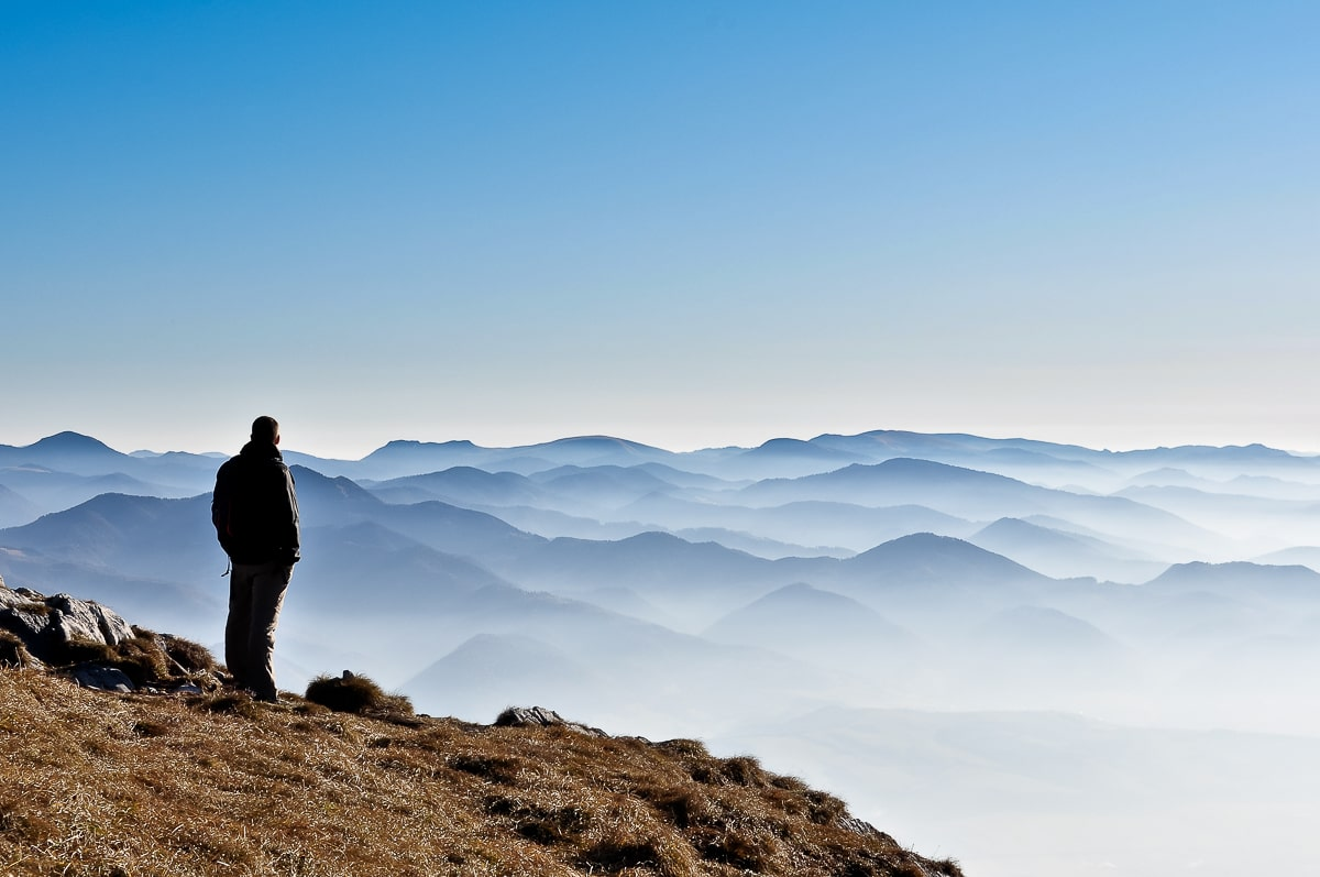 Shadow of man standing on top of mountain with fog and mountains in background how to stop overthinking