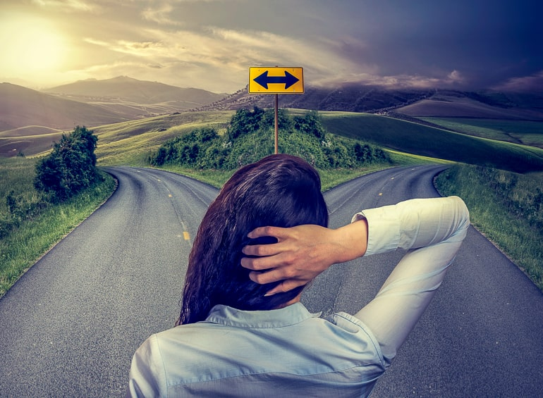 Back of woman standing in front of two streets crossroads stop overthinking tips