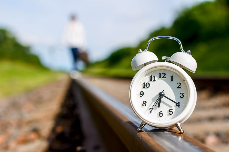 White clock sitting on train tracks with blurry background