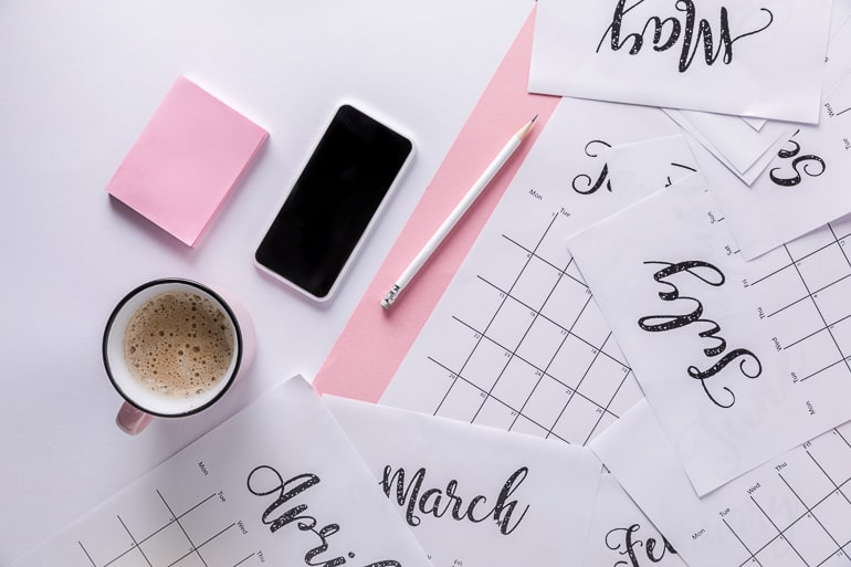 calendar pages on desk with phone and coffee mug