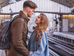 couple standing at train station saying goodbye how to survive a long distance relationship