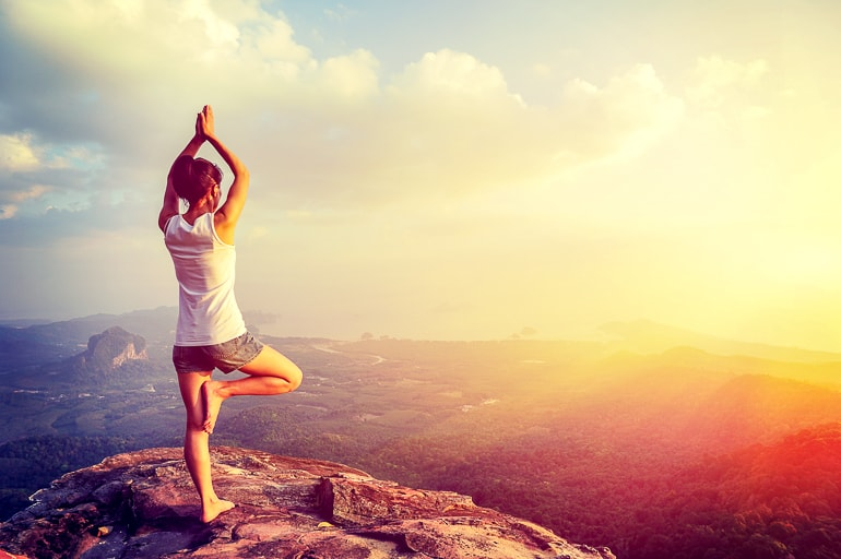 woman in pose on cliff with sun importance of yoga in modern life