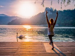 woman on yoga mat on dock with sunrise in front
