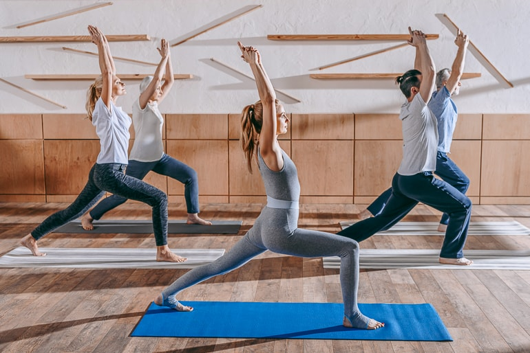 people posing in yoga class with mats underneath importance of yoga in modern life