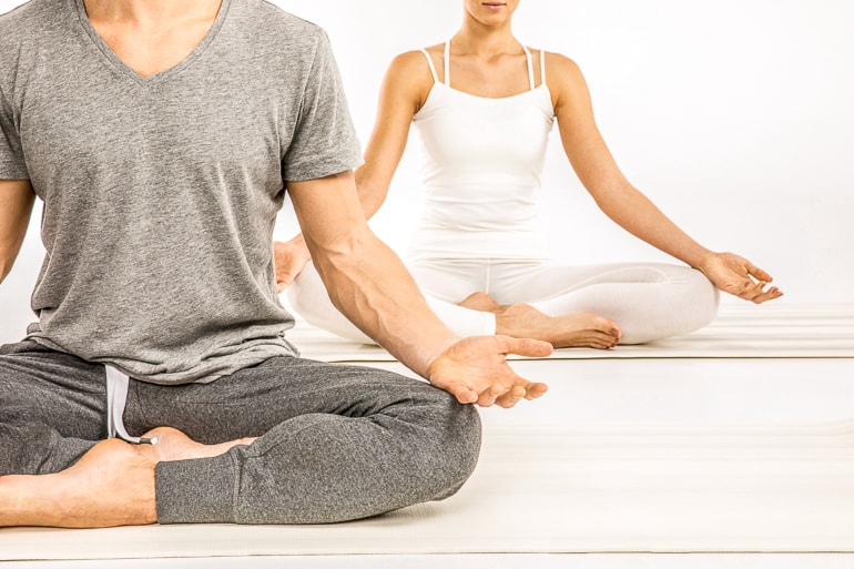 two people sitting on white floor in yoga pose
