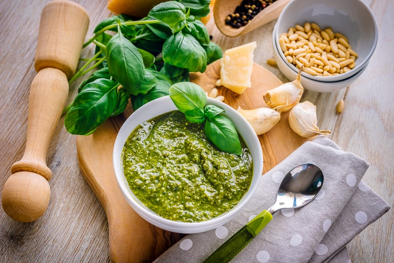 green pesto in white bowl with ingredients around on counter