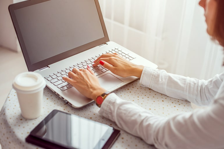 Woman sitting in front of laptop with tablet and cup next to her