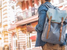 Man with backpack and coffee cup with city houses in background language learning tips