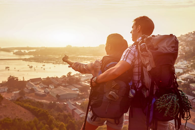couple travelling with backpacks looking at sunset from cliff