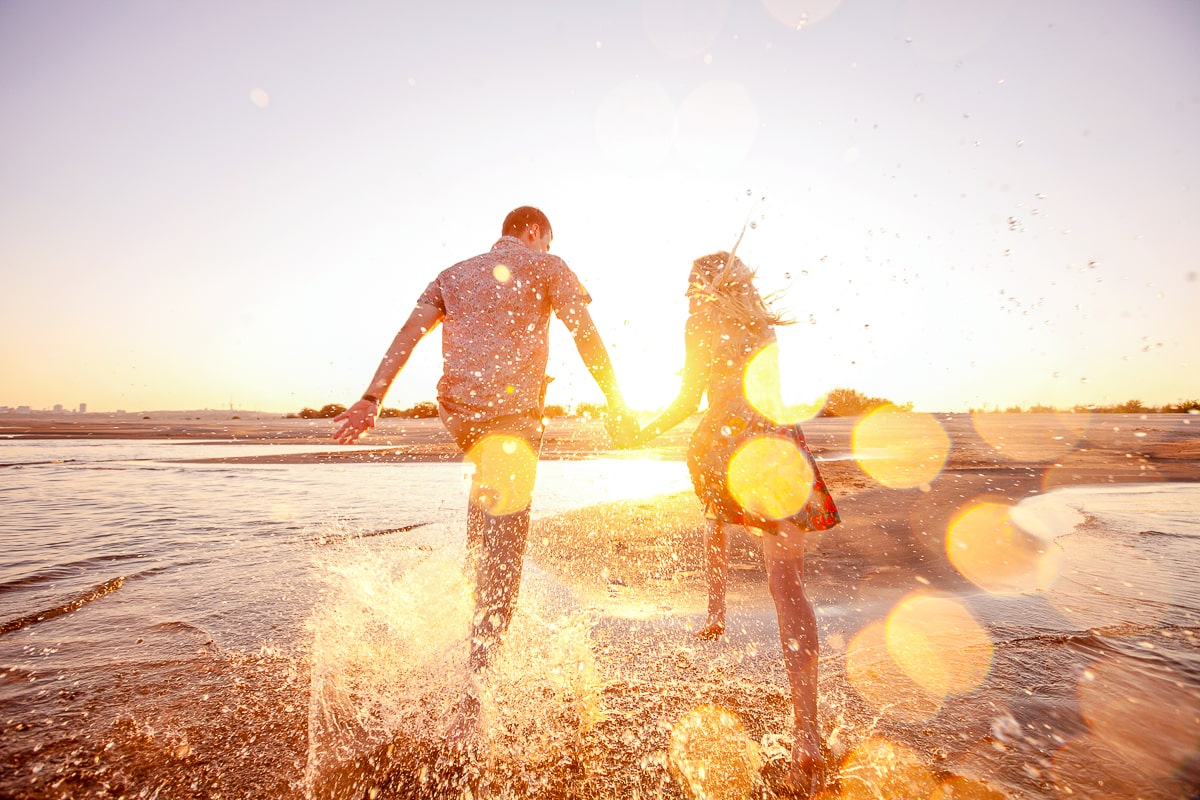 couple running along beach in water with sun shining live in the moment quotes