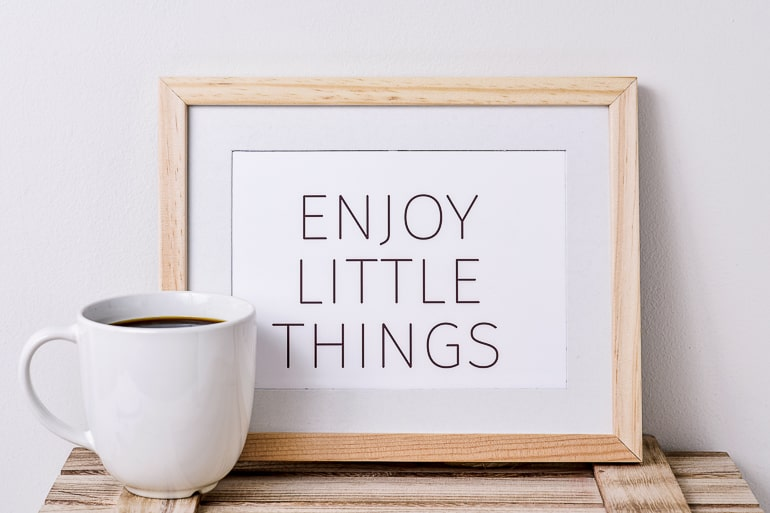 wooden frame with coffee mug live in the moment message