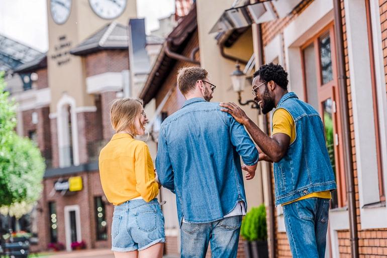 friends walking along sidewalk with backs turned