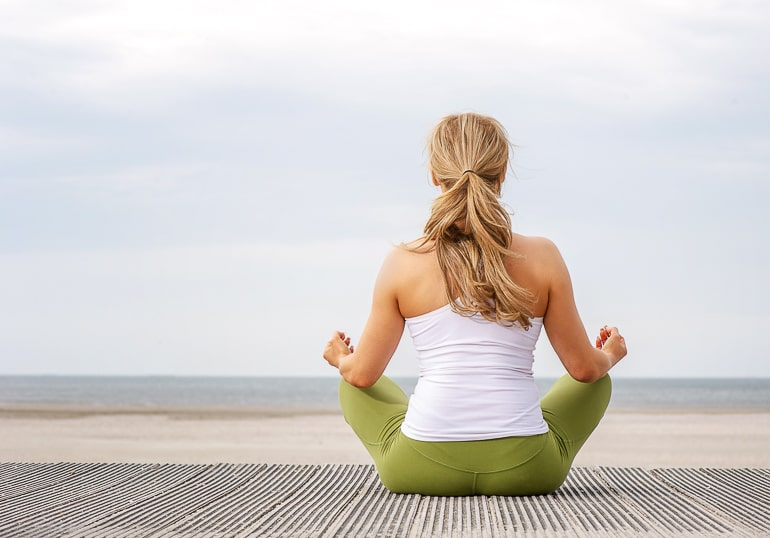 woman with green pants sitting in yoga pose looking at ocean living in the present